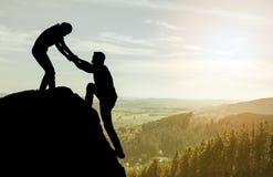 Σκιαγραφία του χεριού βοηθείας μεταξύ του ορειβάτη δύο Στοκ φωτογραφία με δικαίωμα ελεύθερης χρήσης