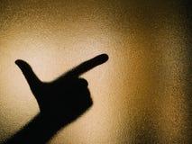 Σκιαγραφία του χεριού που κάνει ένα περίστροφο σε ένα γυαλί στοκ εικόνα με δικαίωμα ελεύθερης χρήσης