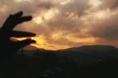 Σκιαγραφία του χεριού που πιάνει τον ήλιο στο ηλιοβασίλεμα στο τοπίο βουνών Στοκ φωτογραφία με δικαίωμα ελεύθερης χρήσης