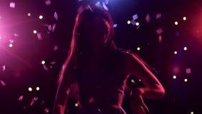 Σκιαγραφία του χορεύοντας κοριτσιού με τα φω'τα και το κομφετί ύφους disco απόθεμα βίντεο