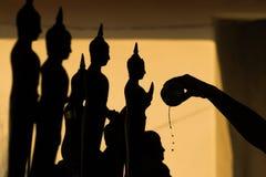 Σκιαγραφία του χύνοντας νερού του Βούδα στο άγαλμα του Βούδα σε Songkran Στοκ Φωτογραφία