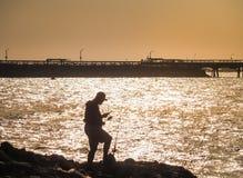 Σκιαγραφία του ψαρά με το λαμπιρίζοντας θαλάσσιο νερό Στοκ εικόνα με δικαίωμα ελεύθερης χρήσης