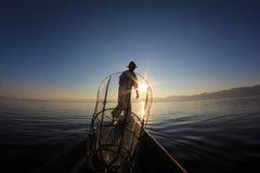 Σκιαγραφία του ψαρά intha ενάντια στον ουρανό ηλιοβασιλέματος Στοκ Φωτογραφίες