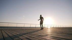 Σκιαγραφία του ψηλού λεπτού νεαρού άνδρα που ασκεί με το άλμα του σχοινιού στην παραλία Άνδρας που συμμετέχεται νεαρός στην εργασ απόθεμα βίντεο