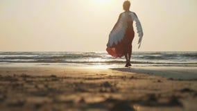 Σκιαγραφία του όμορφου θηλυκού αγγέλου που περπατά χωρίς παπούτσια προς τη θάλασσα στο ηλιοβασίλεμα απόθεμα βίντεο