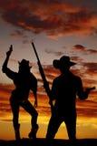 Σκιαγραφία του cowgirl που κρατά ψηλά το πυροβόλο όπλο στον αέρα Στοκ Εικόνες