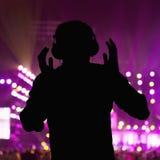 Σκιαγραφία του DJ που φορά τα ακουστικά και που αποδίδει σε μια λέσχη νύχτας Στοκ εικόνα με δικαίωμα ελεύθερης χρήσης