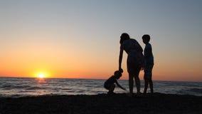 Σκιαγραφία του mom και του γιου στον ωκεανό θάλασσας παραλιών ηλιοβασιλέματος φιλμ μικρού μήκους