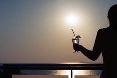 Σκιαγραφία του nude κοριτσιού με το κοκτέιλ στα χέρια στο υπόβαθρο ηλιοβασιλέματος Στοκ φωτογραφία με δικαίωμα ελεύθερης χρήσης