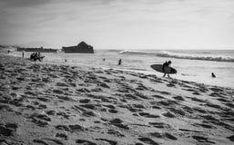 Σκιαγραφία των ανθρώπων στην αμμώδη παραλία που πηγαίνει να κάνει σερφ τα σπάζοντας κύματα του Ατλαντικού Ωκεανού σε γραπτό, capb Στοκ Εικόνες