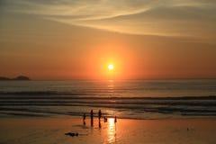 Σκιαγραφία των ανθρώπων στην παραλία και το όμορφο ηλιοβασίλεμα θάλασσας Στοκ φωτογραφίες με δικαίωμα ελεύθερης χρήσης