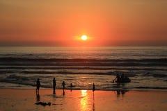 Σκιαγραφία των ανθρώπων στην παραλία και το όμορφο ηλιοβασίλεμα θάλασσας Στοκ Εικόνα