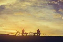 σκιαγραφία των ανθρώπων στο χρόνο ηλιοβασιλέματος Στοκ Φωτογραφίες