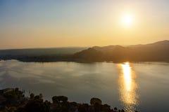 Σκιαγραφία των βουνών και η πόλη Arona στην Ιταλία στο ηλιοβασίλεμα και το νερό Στοκ εικόνες με δικαίωμα ελεύθερης χρήσης