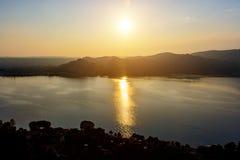 Σκιαγραφία των βουνών και η πόλη Arona στην Ιταλία στο ηλιοβασίλεμα και το νερό Στοκ Εικόνες