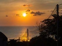 Σκιαγραφία των ηλεκτρικών καλωδίων ενάντια στον ήλιο που θέτει στη θάλασσα στοκ εικόνα