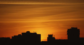 Σκιαγραφία των κτηρίων στο πορτοκαλί ηλιοβασίλεμα, σκιαγραφίες κτηρίων στο ζωηρόχρωμο ηλιοβασίλεμα, που εξισώνουν στην πόλη, φλεμ Στοκ Εικόνα