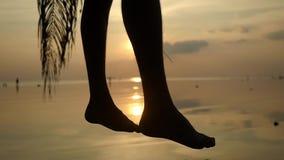 Σκιαγραφία των κυματίζοντας αρσενικών ποδιών στην τροπική παραλία κατά τη διάρκεια του όμορφου ηλιοβασιλέματος Ο νεαρός άνδρας κά απόθεμα βίντεο