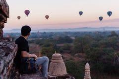 Σκιαγραφία των νέων αρσενικών προορισμών ταξιδιού μπαλονιών ζεστού αέρα συνεδρίασης και προσοχής backpacker σε Bagan, το Μιανμάρ Στοκ Εικόνες
