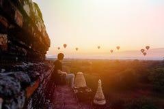 Σκιαγραφία των νέων αρσενικών προορισμών ταξιδιού μπαλονιών ζεστού αέρα συνεδρίασης και προσοχής backpacker σε Bagan, το Μιανμάρ Στοκ Φωτογραφία