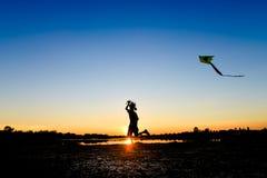 Σκιαγραφία των παιδιών που πετούν έναν ικτίνο στο ηλιοβασίλεμα Στοκ Φωτογραφία