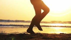 Σκιαγραφία των ποδιών του κοριτσιού που πηδούν στο σχοινί στην παραλία άμμου θάλασσας στο ηλιοβασίλεμα απόθεμα βίντεο