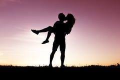 Σκιαγραφία των ρομαντικών εραστών με το ηλιοβασίλεμα στην πλάτη Στοκ Φωτογραφία