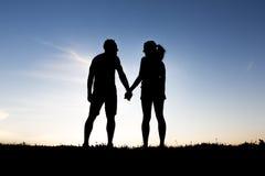 Σκιαγραφία των ρομαντικών εραστών με το ηλιοβασίλεμα στην πλάτη Στοκ Εικόνες