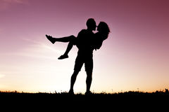 Σκιαγραφία των ρομαντικών εραστών με το ηλιοβασίλεμα στην πλάτη Στοκ φωτογραφία με δικαίωμα ελεύθερης χρήσης