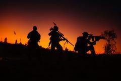 Σκιαγραφία των στρατιωτικών στρατιωτών με τα όπλα τη νύχτα πυροβολισμός, hol Στοκ Εικόνες