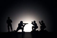 Σκιαγραφία των στρατιωτών σε ένα σκοτεινό υπόβαθρο στοκ εικόνα