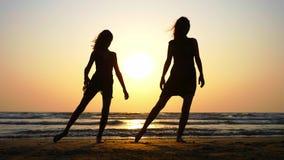 Σκιαγραφία των φίλαθλων νέων γυναικών που ασκούν το χορεύοντας στοιχείο στην παραλία απόθεμα βίντεο