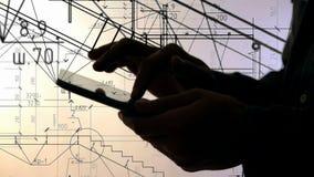 Σκιαγραφία των χεριών που χρησιμοποιούν το PC ταμπλετών λειτουργώντας με τα σχεδιαγράμματα φιλμ μικρού μήκους