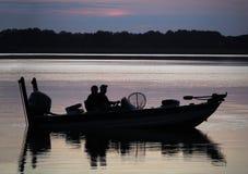 Σκιαγραφία των ψαράδων στη βάρκα στην ανατολή στοκ εικόνα