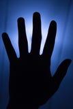Σκιαγραφία χεριών με το γαλαζωπό υπόβαθρο Στοκ Φωτογραφίες