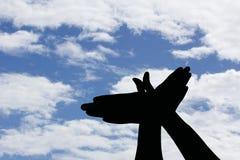 Σκιαγραφία χεριών μορφής πουλιών στο μπλε ουρανό, ελευθερία έννοιας Στοκ Φωτογραφία