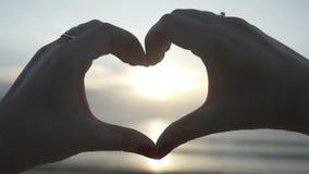 Σκιαγραφία χεριών των νέων γυναικών που φορούν τα δαχτυλίδια που κάνουν μια μορφή καρδιών με το ηλιοβασίλεμα μέσα στην παραλία σε απόθεμα βίντεο