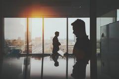 Σκιαγραφία δύο επιχειρηματιών στο εσωτερικό γραφείων Στοκ εικόνες με δικαίωμα ελεύθερης χρήσης