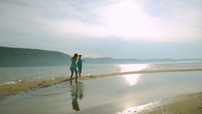 Σκιαγραφία δύο νέων γυναικών που τρέχουν γύρω από και που πηδούν στην αμμώδη παραλία στο ηλιοβασίλεμα Φιλία, θερινές διακοπές απόθεμα βίντεο