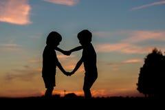 Σκιαγραφία δύο παιδιών, αδελφοί αγοριών, που κατασκευάζουν την καρδιά να διαμορφώσει το πνεύμα Στοκ Φωτογραφία