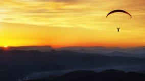 Σκιαγραφία Paraglide πέρα από τα βουνά στο ηλιοβασίλεμα Στοκ Εικόνες