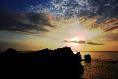Σκιαγραφία seascape και του βράχου με το χρυσό φως Στοκ Φωτογραφίες