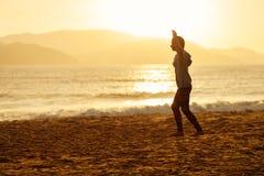 Σκιαγραφία slackline ισορροπίας έφηβη στην παραλία Στοκ Εικόνες