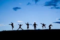 Σκιαγραφίες έξι παιδιών που πηδούν μαζί στο μπλε ουρανό Στοκ φωτογραφία με δικαίωμα ελεύθερης χρήσης