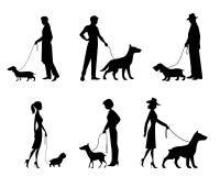 Σκιαγραφίες ανθρώπων με τα σκυλιά Απεικόνιση αποθεμάτων