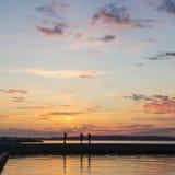 Σκιαγραφίες ανθρώπων στην αποβάθρα λιμνών το βράδυ Στοκ Εικόνες