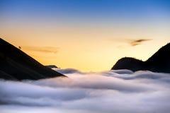 Σκιαγραφίες βουνών και ομίχλη στην κοιλάδα, ανατολή Στοκ Εικόνες