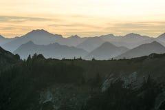 Σκιαγραφίες βουνών με το δασικό και πορτοκαλή ουρανό στοκ εικόνα