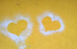 Σκιαγραφίες δύο καρδιών σε έναν κίτρινο συμπαγή τοίχο στοκ φωτογραφίες