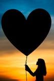 Σκιαγραφίες ενός κοριτσιού και ενός μπαλονιού Στοκ Εικόνες